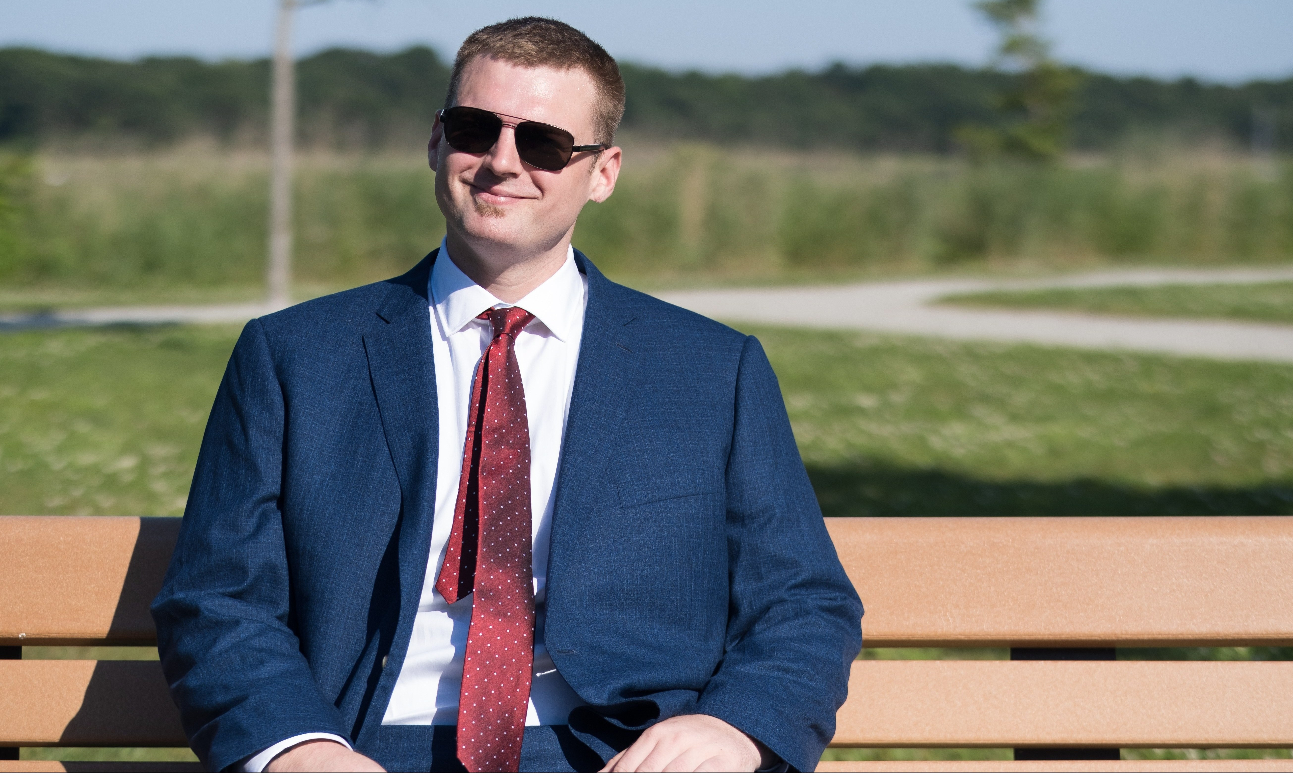 Ed sits on a bench in Webb Park in North Weymouth. Tall grass is visible in the distance, and the sky is clear and blue overhead. He's wearing a blue suit jacket, a red tie, and sunglasses, and smiling.