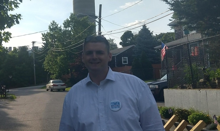 Ed smiles on a street in North Weymouth. An industrial tower and power lines are visible behind him. The sky is blue with scant clouds overhead.